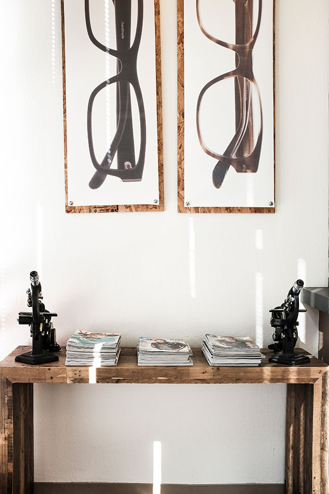The art pieces were a weekend DIY project my husband made. In this composition are elements of wood, metal, concrete and fabric. The whimsyare the vintage lens readers that I found in the back of a cabinet from the previous owner.Photo appears courtesy of Andrew Wong photography .